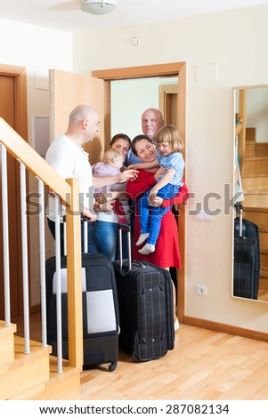 Happy family with children seeing off the relatives to home - stock photo
