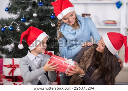 Happy family with Christmas gifts. Christmas tree and gifts in background. - stock photo