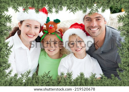 Happy family with christmas hats sitting on the sofa against green fir branches - stock photo