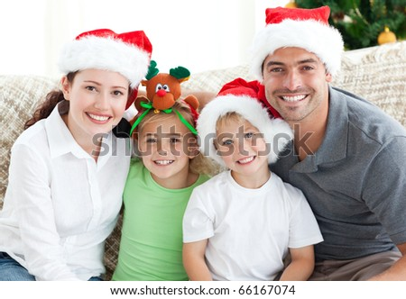 Happy family with Christmas hats sitting on the sofa at home