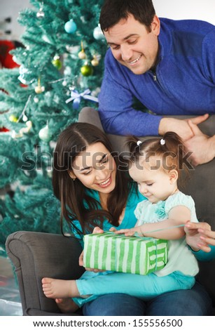 Happy family with Christmas present near the Christmas tree - stock photo