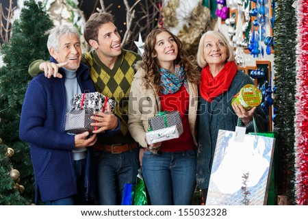 Happy family with Christmas presents and bags shopping in store - stock photo