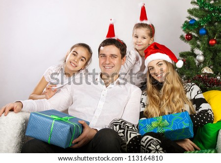 Happy family with Christmas presents near the Christmas tree - stock photo