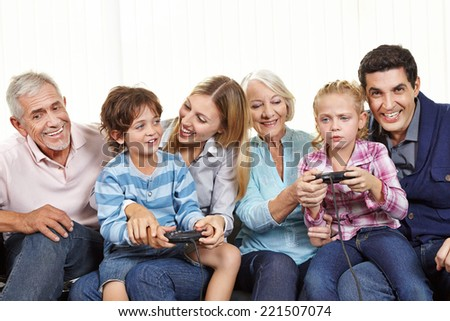Happy family with controller playing video games on Smart TV in living room - stock photo