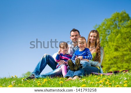 Happy family with daughter and son sitting in a meadow in summer