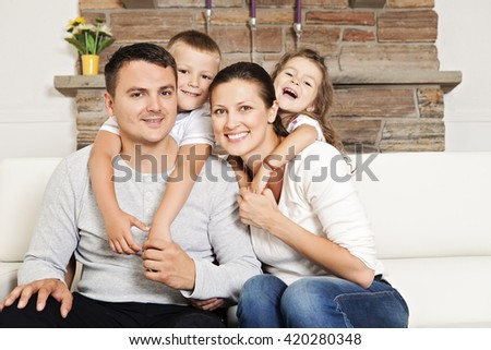 Happy family with daughter and son sitting on the couch - stock photo
