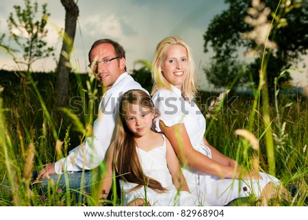 Happy family with daughter girl sitting in a meadow in summer before a thunder storm