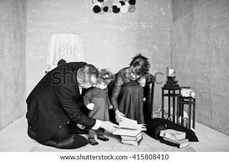 Happy family with daughter read the old book on rugs background vintage room with decor - stock photo