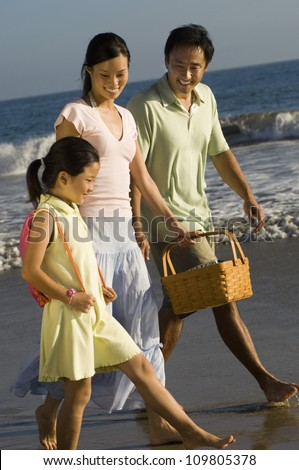 Happy family with daughter walking together on beach