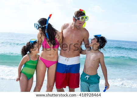 Happy family with diving goggles standing on sea shore at beach