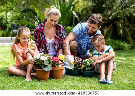 Happy family with flower pots sitting on grass at yard