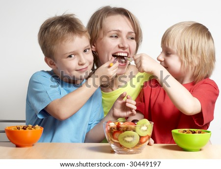 Happy family with fruit salad - stock photo