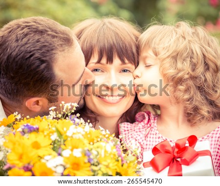 Happy family with gift box and beautiful flowers against green background. Spring holiday concept. Mothers day - stock photo