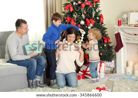 Happy family with gift boxes in home holiday living room, at morning