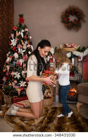 Happy family with  gifts standing near Christmas tree at home. Merry Christmas and New Year. - stock photo