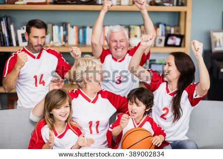 Happy family with grandparents watching basketball match at home - stock photo