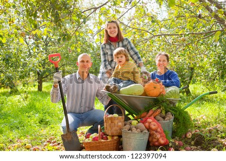 Happy  family with  harvest in vegetable garden - stock photo