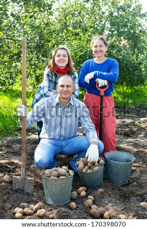 Happy family with harvested potatoes in field - stock photo