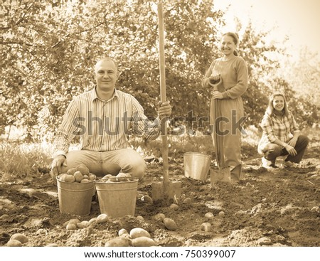 Happy family with harvested potatoes in field