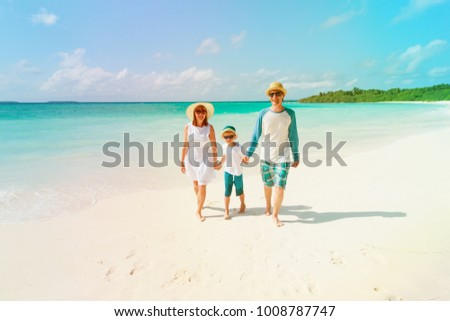 happy family with kid walking on beach
