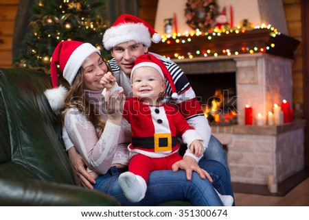 Happy family with kid weared Santa sitting on sofa in front of Christmas tree and fireplace  in living room