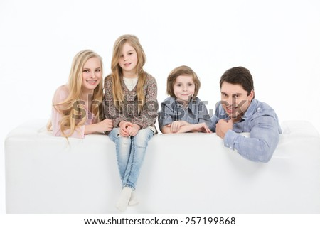 Happy family with kids on the couch white background - stock photo