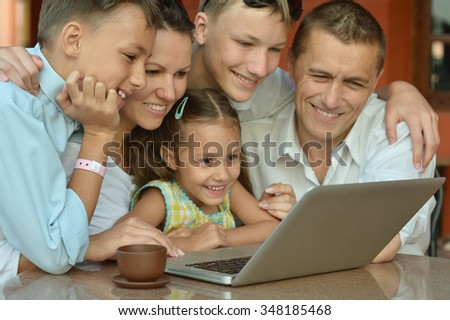 happy family  with laptop at the table - stock photo