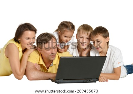 Happy family with laptop on a floor