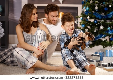 Happy family with little boy and dachshund puppy at christmas morning.