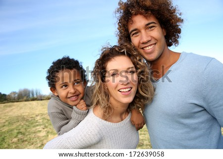 Happy family with little boy in countryside - stock photo
