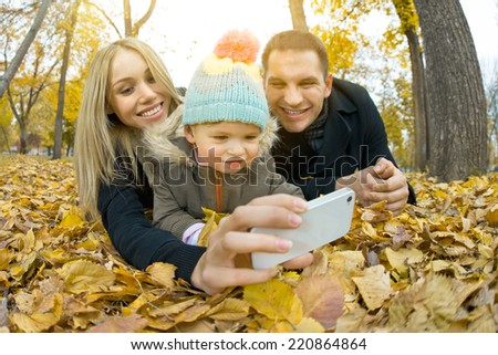 happy family with little child take Selfie on telephone, outing in autumn park - stock photo
