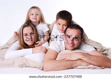 happy family with little children playing in bed  - stock photo
