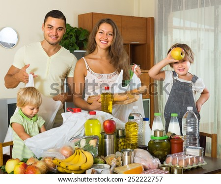 Happy family with little children sorting purchased food out indoor
