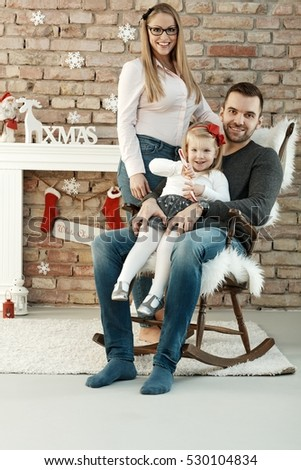 Happy family with little daughter smiling at christmas time.