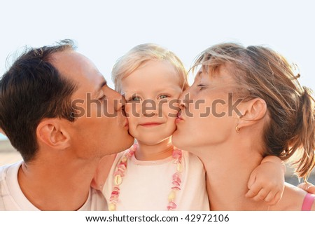 Happy family with little near to sea, parents kiss daughter - stock photo