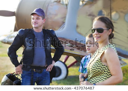 Happy family with little son near the vintage airplane