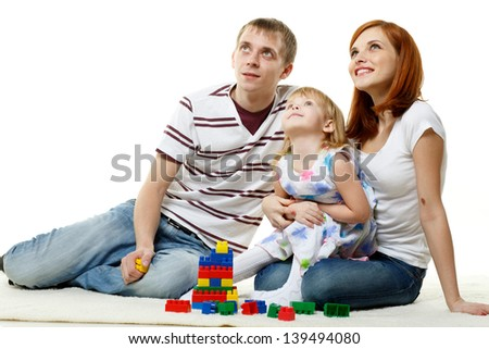 Happy family with lovely daughter build house on a white background.  Concept of  building and purchase  of the house. - stock photo