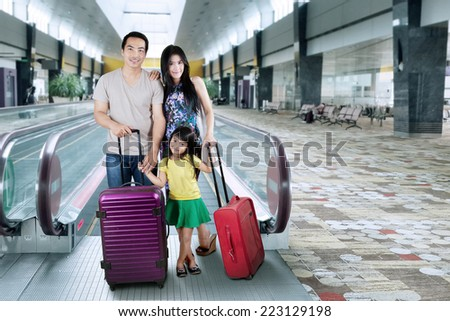 Happy family with luggage in holiday trip standing on airport hall - stock photo