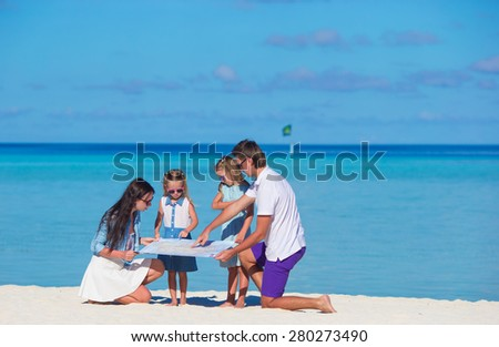Happy family with map on the beach