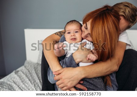 Happy family with newborn baby on the bed in the room