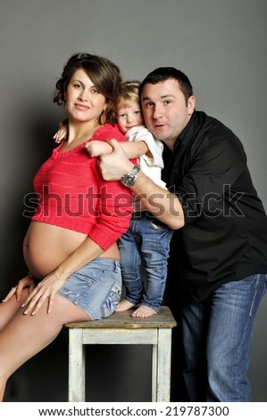 Happy family with pregnant woman on gray background - stock photo