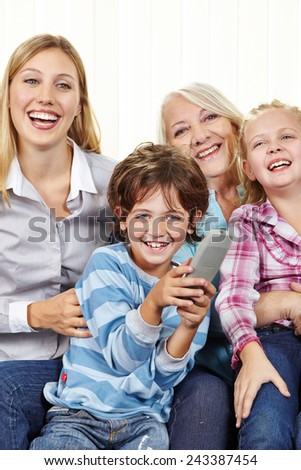 Happy family with remote control watching TV in living room