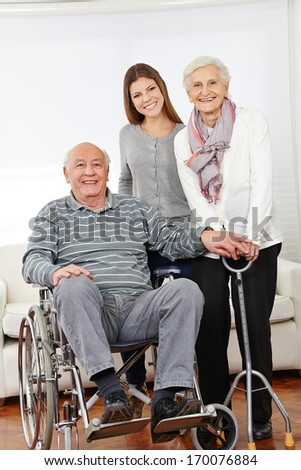 Happy family with senior citizen couple and granddaughter at home - stock photo