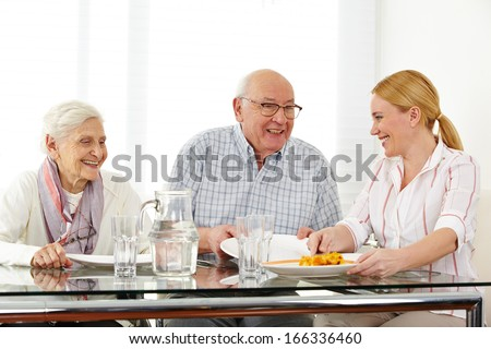 Happy family with senior couple eating lunch at table - stock photo