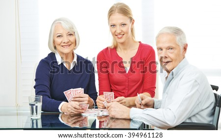 Happy family with senior people playing cards at home - stock photo