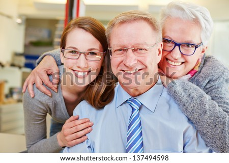 Happy family with seniors at optician with their new glasses - stock photo