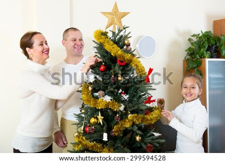 Happy family with small daughter at Christmas time or winter holiday season  at home. - stock photo