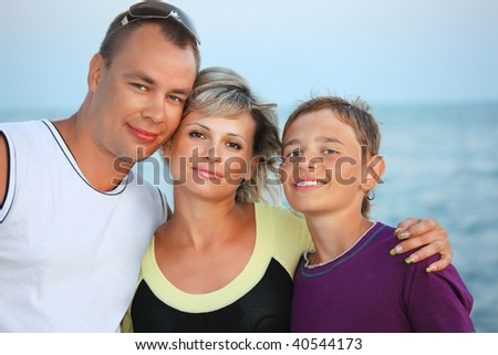 Happy family with smiling boy on beach in evening