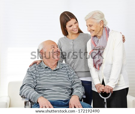 Happy family with smiling senior couple at home - stock photo