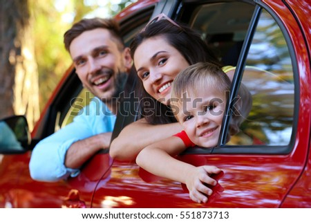 Happy family with son sitting in car on sunny day
